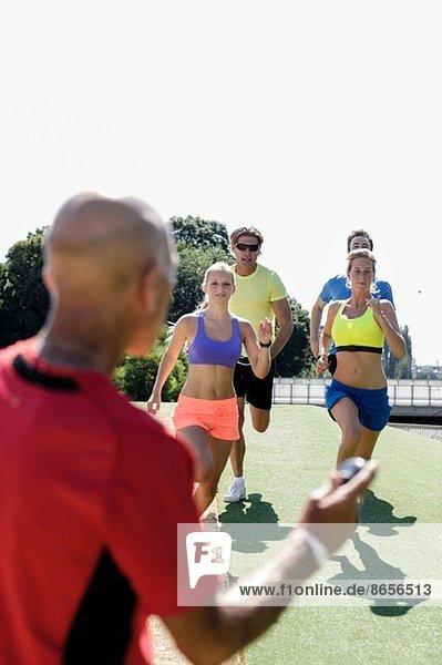 Erwachsener Mann  der eine Gruppe erwachsener Läufer trainiert.