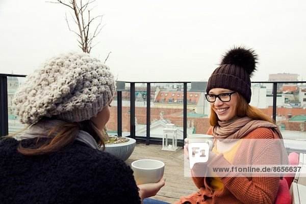 Two young adult women having coffee on rooftop terrace