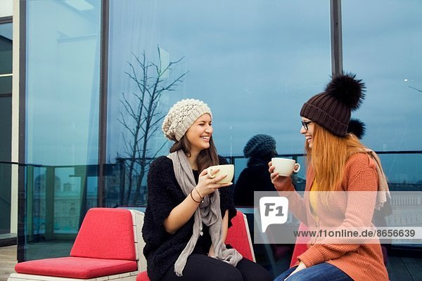 Two young adult women enjoying coffee on rooftop terrace