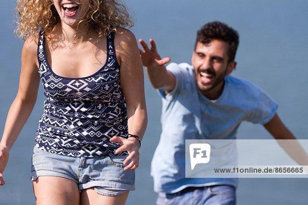 Junger Mann jagt Frau  lacht.