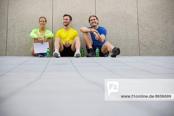 Drei Freunde sitzen auf dem Boden und tragen Sportbekleidung.