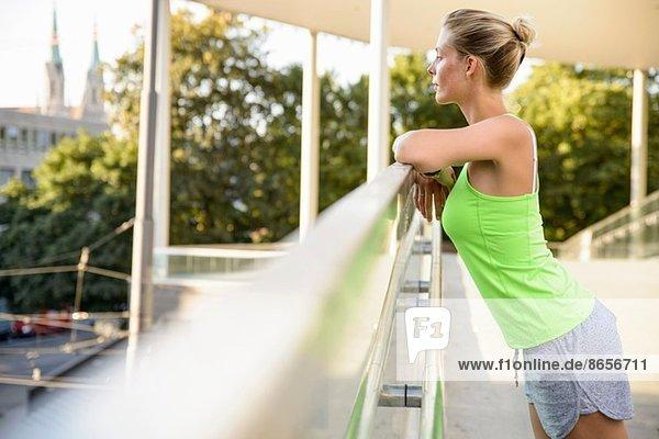 Junge Frau  die sich auf das Geländer stützt