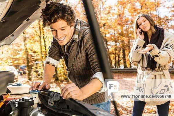 Mann auf der Motorhaube  Frau am Handy