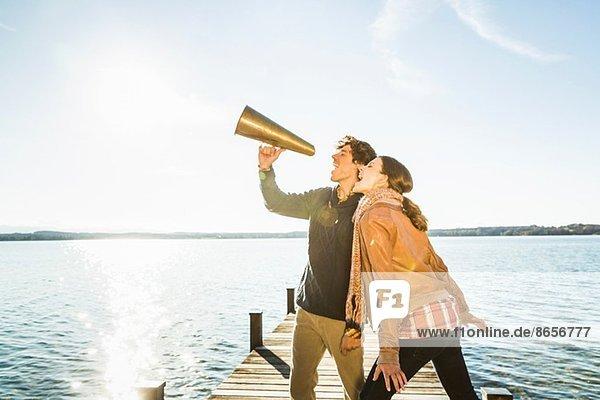 Paar mit Megaphon am See