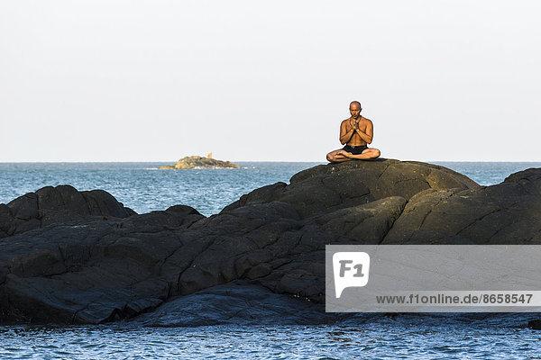 Ein Mann in Meditation  Yoga auf einem Felsen  Kudle Beach  Gokarna  Karnataka  Indien