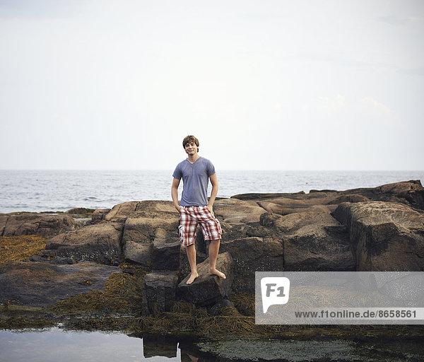 Ein junger Mann steht am Ufer an einem Felsenbecken mit den Händen in den Taschen.