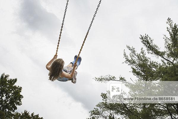 Ein Mädchen auf einer Seilschaukel  hoch in der Luft
