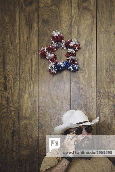 Mann mit langem Bart und Cowboyhut beim Telefonieren.