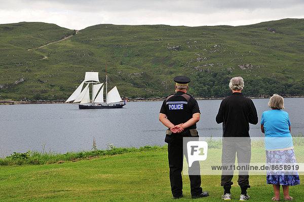 Menschen am Ufer betrachten den niederländischen Zweimast-Topschoner Wylde Swan auf dem Loch Broom  Ullapool  Caithness  Sutherland and Ross  Highlands  Schottland  Großbritannien