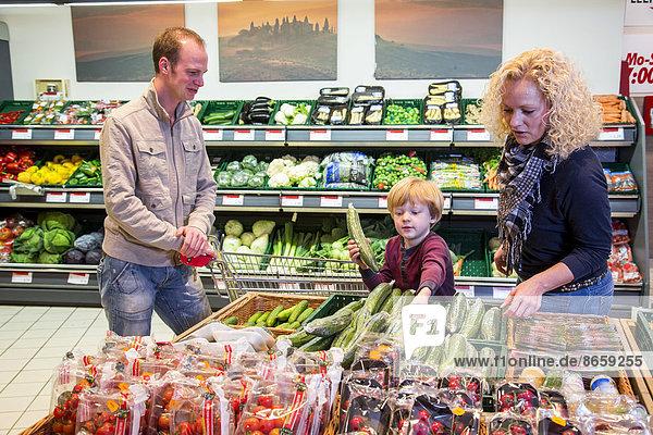 Familie mit Einkaufswagen beim Einkaufen im Supermarkt  Gemüseabteilung  Deutschland