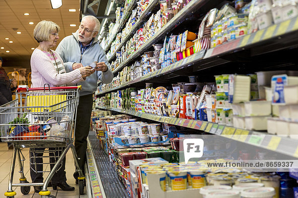 Senior couple shopping with a shopping trolley in the refrigerated dairy section in a supermarket  Germany