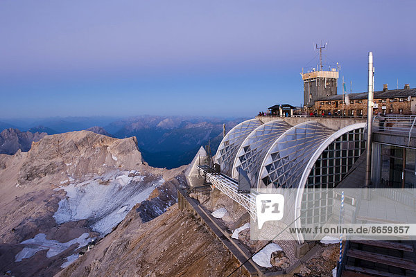 Summit plateau of Mt Zugspitze with a terrace and Münchner Haus mountain hut  at dawn before sunrise  Bavaria  Germany