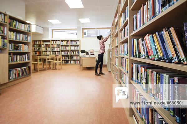 Frau sucht ein Buch in einer Schulbibliothek  Reit im Alpbachtal  Tirol  Österreich