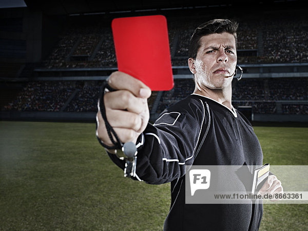 Schiedsrichter blinkt rote Karte auf dem Fußballfeld