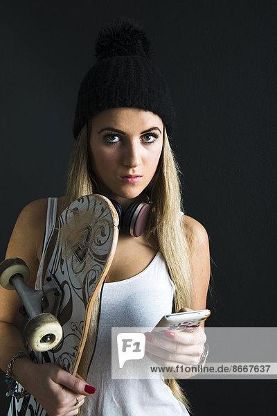 Junge Frau mit Skateboard und Mütze
