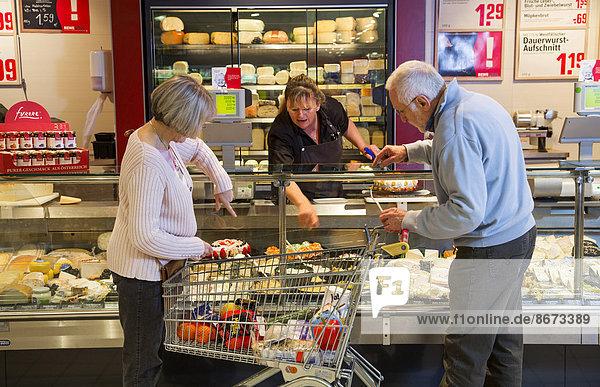 Seniorenpaar mit Einkaufswagen beim Einkaufen im Supermarkt  an der Käsetheke  Deutschland