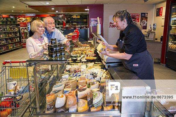 Verkäuferin bedient ein Seniorenpaar an der Käsetheke  beim Einkaufen im Supermarkt  Deutschland