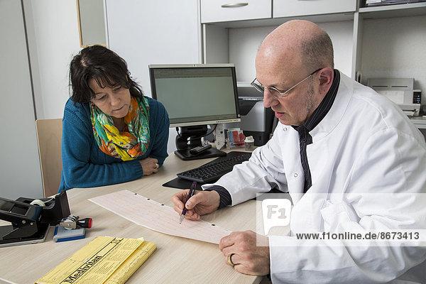 Arztpraxis  Arzt unterhält sich mit einer Patientin über einen EKG-Befund  Deutschland