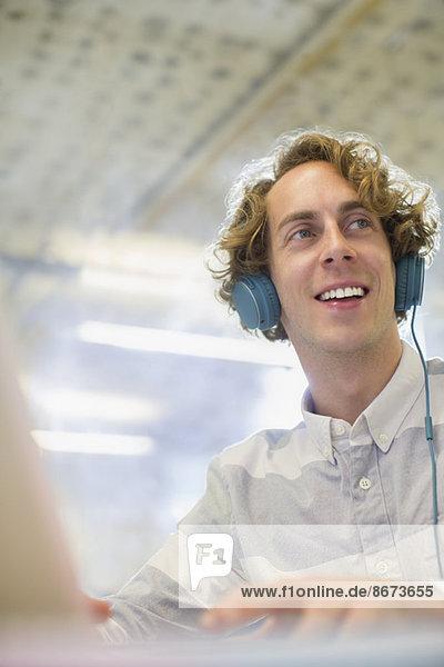Geschäftsmann hört Kopfhörer im Büro