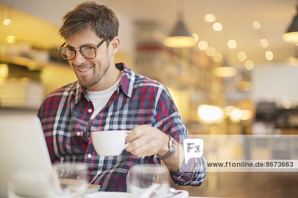 Mann mit Laptop und Kaffeetrinken im Cafe