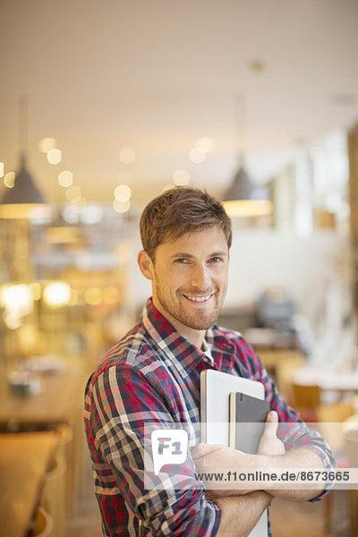 Mann mit Büchern im Café