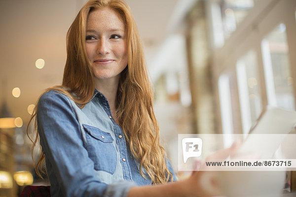 Frau mit digitalem Tablett im Cafe