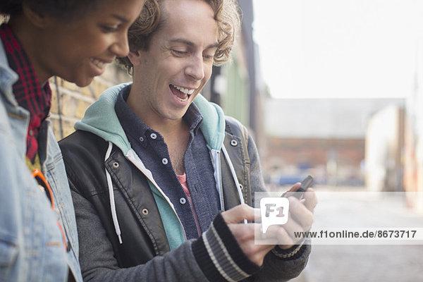 Paar mit dem Handy auf der Stadtstraße