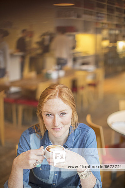 Frau trinkt eine Tasse Kaffee im Café