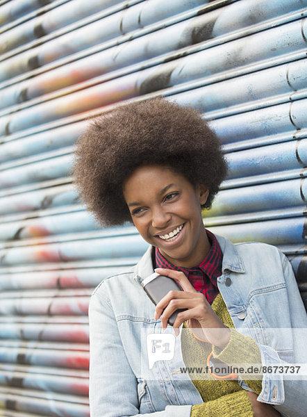 Frau mit Handy lächelt gegen Graffiti-Wand