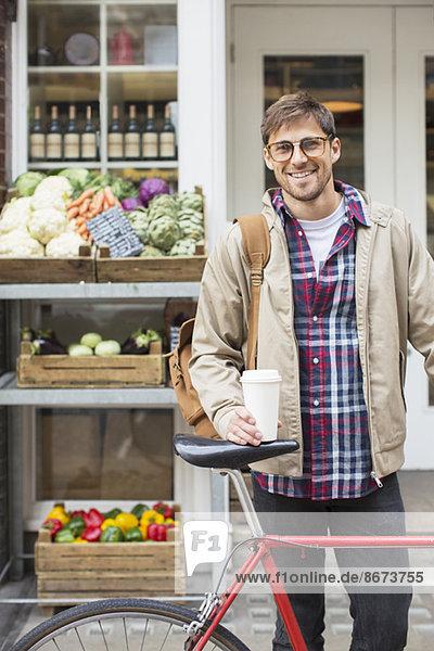 Mann mit Kaffeetasse und Fahrrad auf der Stadtstraße