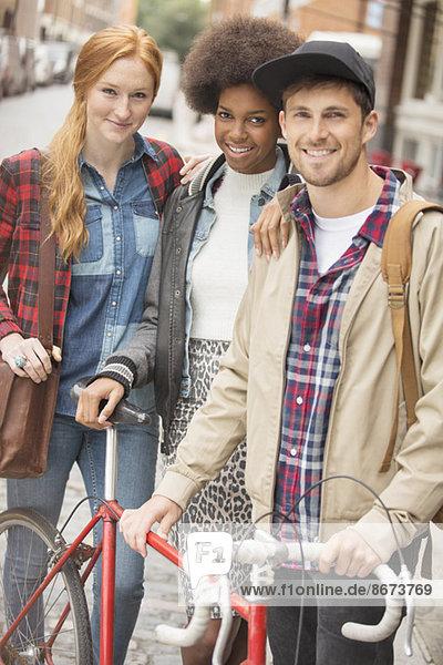 Freunde lächeln zusammen auf der Stadtstraße
