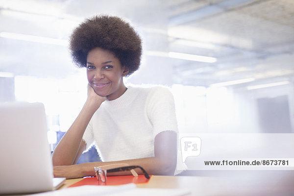 Geschäftsfrau lächelt am Schreibtisch im Büro