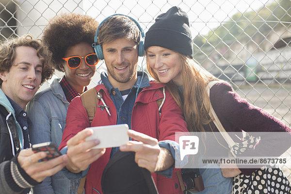 Freunde beim Selbstporträt mit Fotohandy im Freien