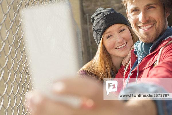 Selbstporträt eines Paares mit Fotohandy neben dem Kettengliederzaun
