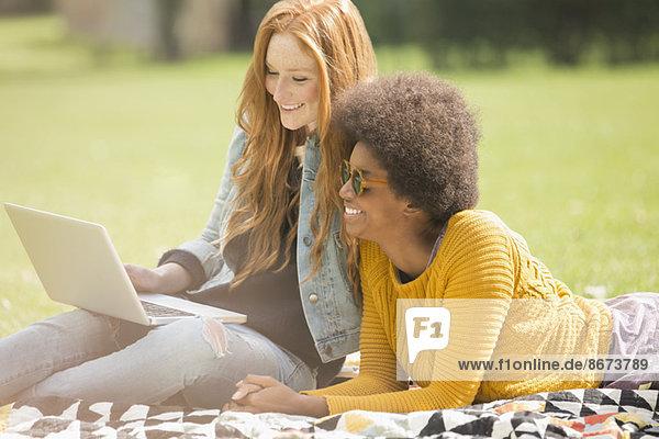 Frauen  die ihren Laptop zusammen im Park benutzen