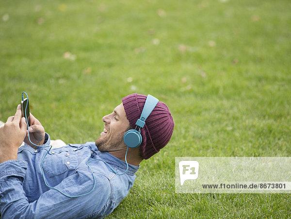 Mann hört Kopfhörer im Park