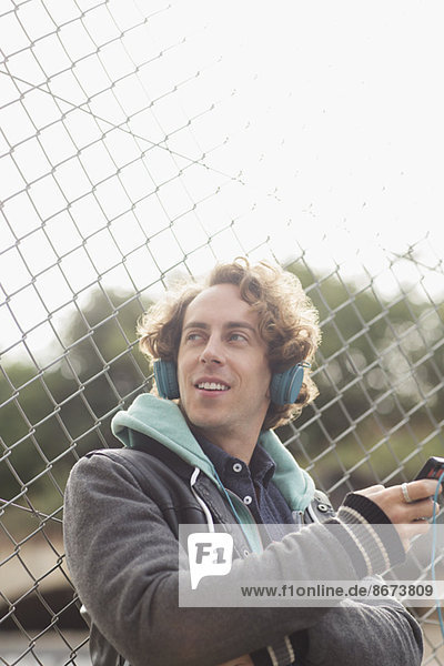 Mann hört Kopfhörer gegen Kettengliedzaun