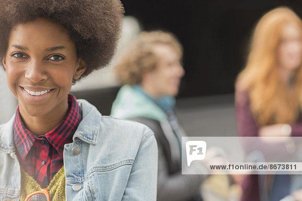 Frau lächelt mit Freunden im Hintergrund