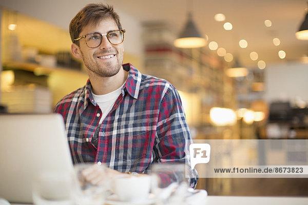 Mann mit Laptop im Café