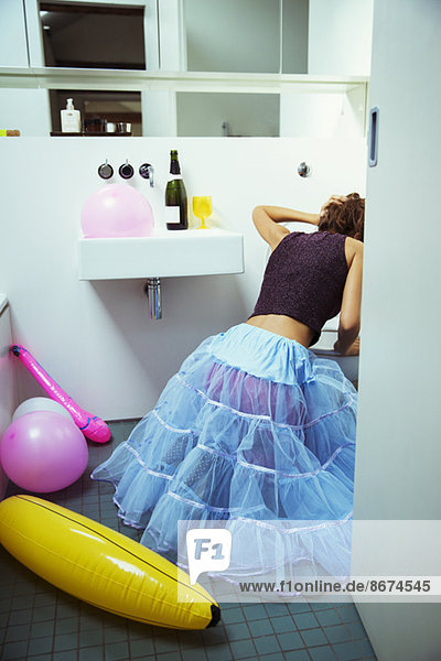 Frau erbricht auf der Party in die Toilette