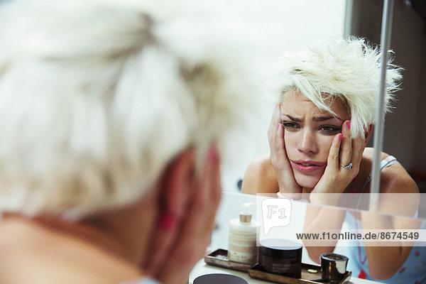 Hungover Frau untersucht sich im Spiegel