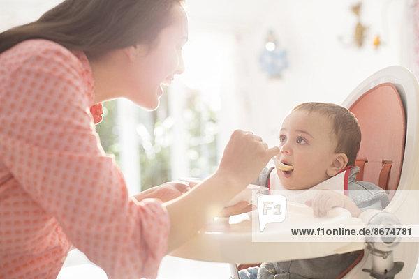 Mutter füttert den Jungen im Hochstuhl