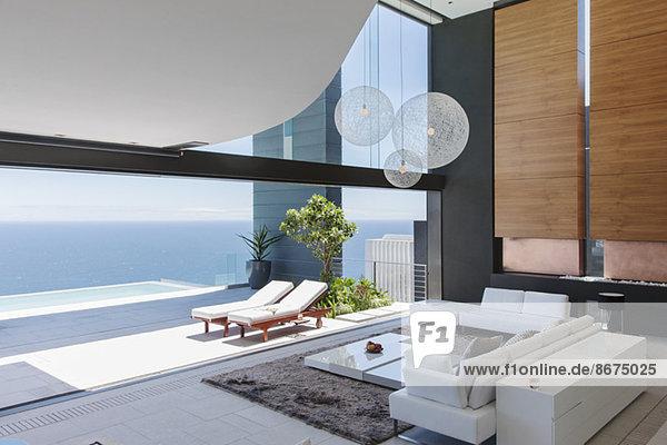 Wohnzimmer und Terrasse des modernen Hauses mit Blick auf den Ozean