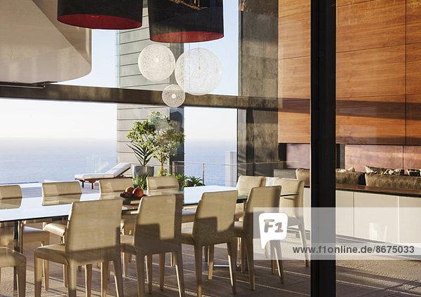 Tisch und Stühle im modernen Esszimmer mit Meerblick