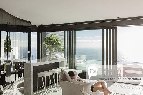 Frau entspannt sich im modernen Wohnzimmer mit Blick aufs Meer