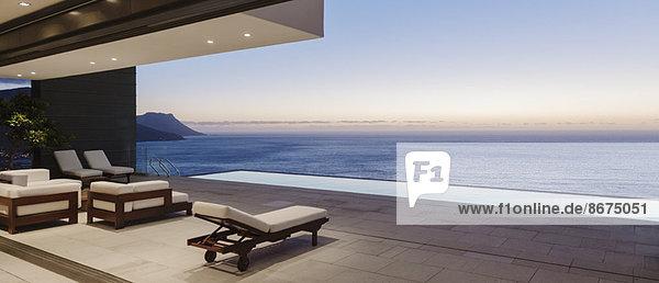 Moderne Terrasse und Infinity-Pool mit Blick auf das Meer bei Sonnenuntergang
