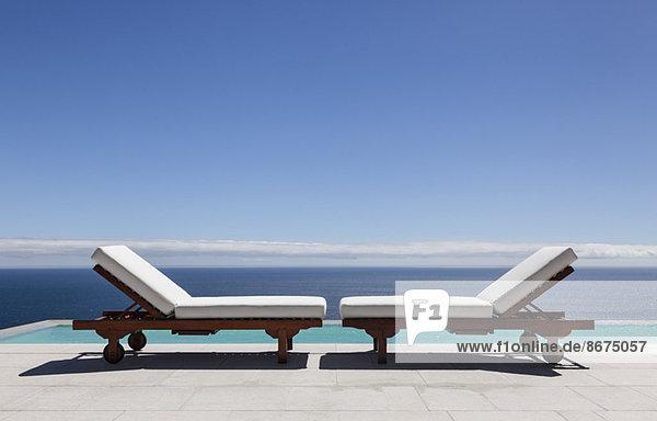 Liegestühle und Infinity-Pool mit Blick auf das Meer