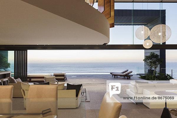 Modernes Wohnzimmer mit Blick auf das Meer bei Sonnenuntergang