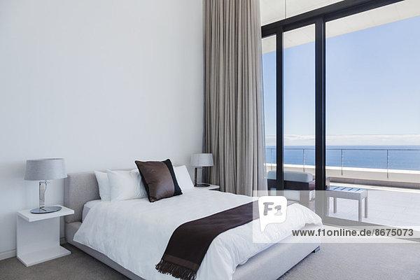 Bett und Lampen im modernen Schlafzimmer mit Blick aufs Meer