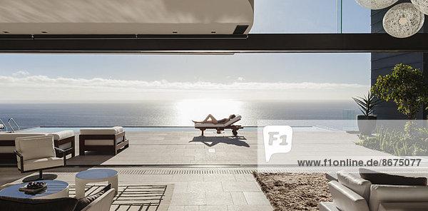 Frau beim Sonnenbaden auf einem Liegestuhl am Pool mit Blick auf den Ozean